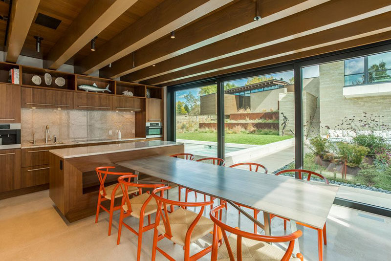 This wooden kitchen has light countertops and enough space for a dining table that seats eight.