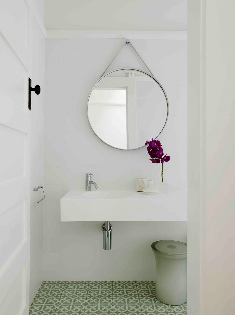 This contemporary bathroom has a round mirror hanging above the minimal white vanity, and a patterned green and white tile covers the floor to add some color to the space.