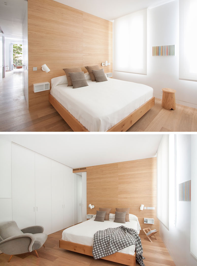 In this modern bedroom, white walls and window shades are broken up by light wood details, like the floor, accent wall and bed frame. Opposite the windows is a wall of white cabinetry that almost blends in to the surrounding wall.