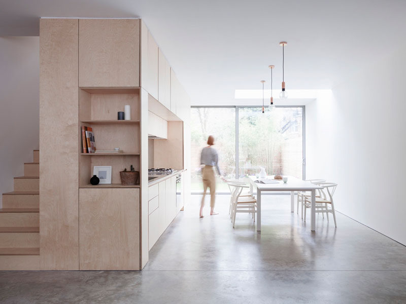 Kitchen Ideas - At the end of this contemporary wood kitchen, open shelving and stairs made from the same light wood as the kitchen cabinets helps to create a cohesive look within the home.