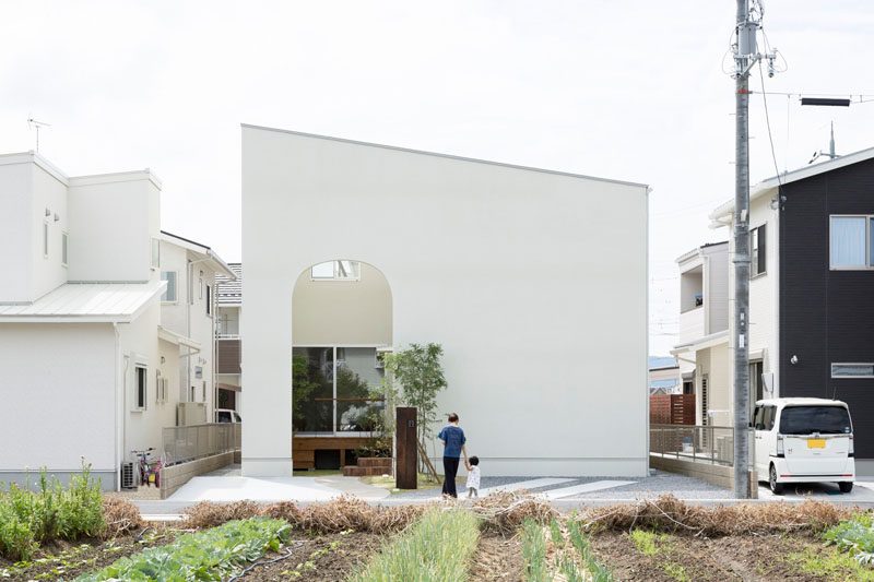 12 Minimalist Modern House Exteriors // An all white exterior wall provides privacy for the home and makes the exterior of the house look simple and modern with the angled roof and arched entrance.