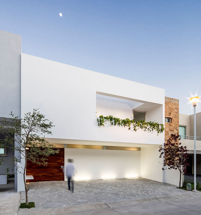 12 Minimalist Modern House Exteriors // The oversized wood door and dripping greenery on the front of this house warm up the white and make the minimalist exterior more inviting.