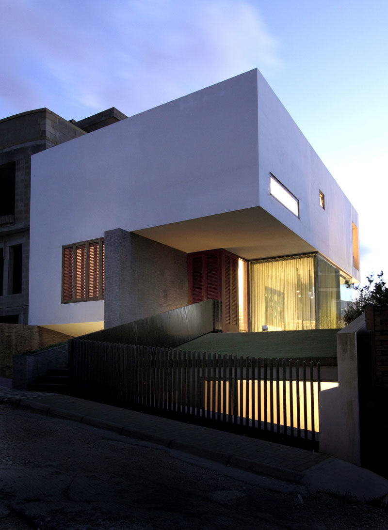 The clean lines, warm materials, and white exterior of this house look minimal, modern, and inviting.