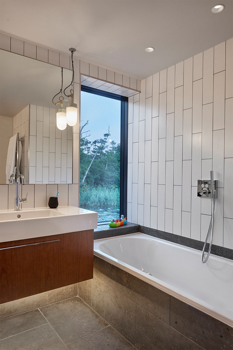 In this modern bathroom, large white tiles have been installed vertically adding to the sense of height in the room, and a tall window allows for views when taking a bath. A wood vanity is topped with a white countertop, and concrete tiles have been used for the floor and bath surround.