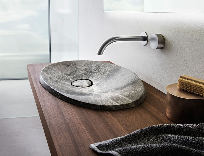 This Modern Bathroom Sink Made From Natural Stone Sits On A Floating Wood Vanity And Has