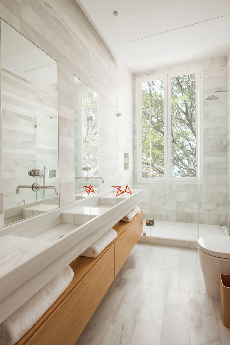 In this modern bathroom there's a wooden bathroom vanity with open shelving, that has double sinks with tall rectangular mirrors above each one. A glass shower surround allows the light from the vertical windows to pass through and fill the room, while stone tile adds a soft natural touch to the space.
