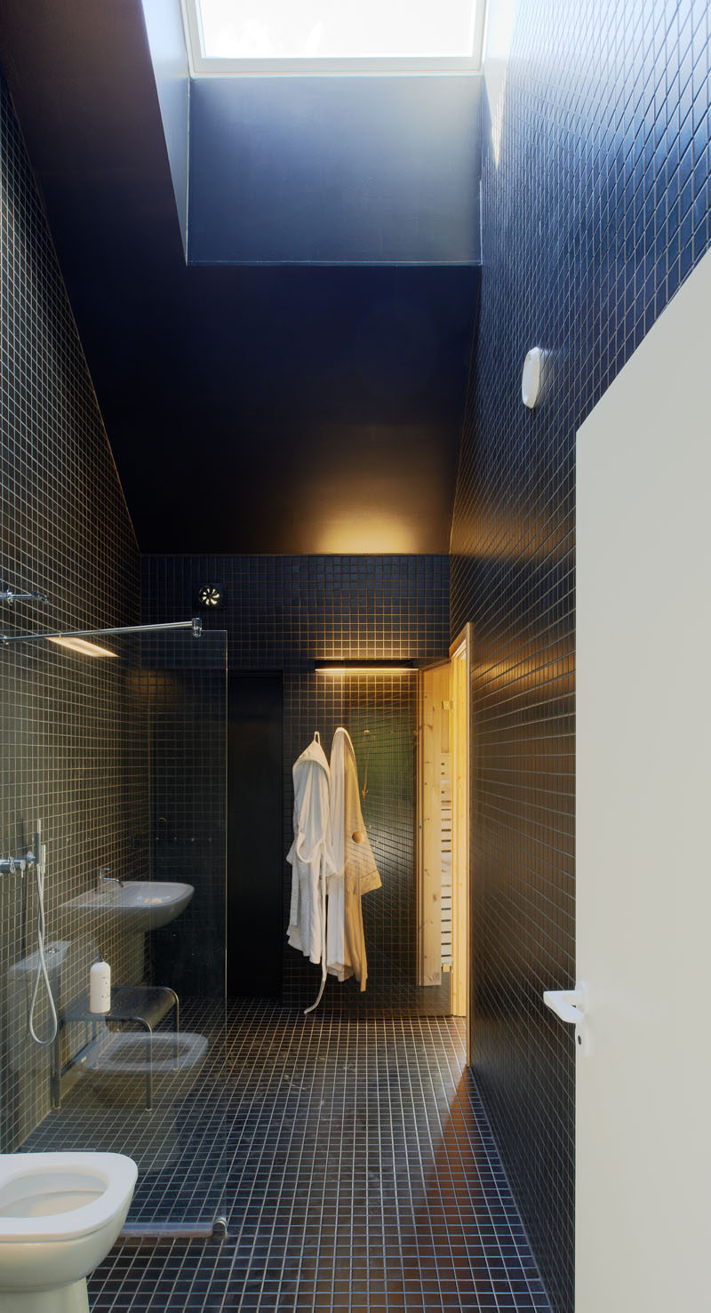 Bathroom Tile Idea - Use The Same Tile On The Floors And The Walls | Small, square, deep blue tiles cover the floors and walls of the bathroom in this family home.