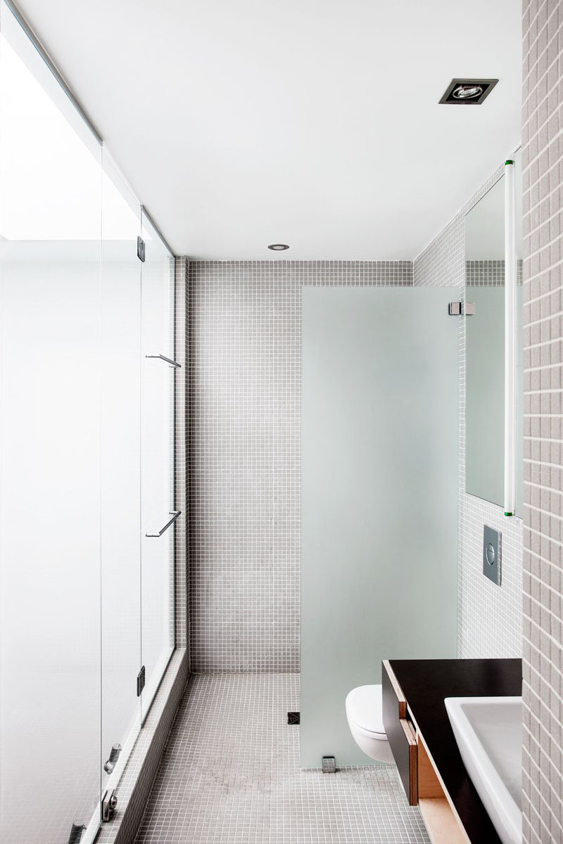 Bathroom Tile Idea - Use The Same Tile On The Floors And The Walls | Grey tiles used on the floors and walls of this bathroom create a neutral and relaxing space.