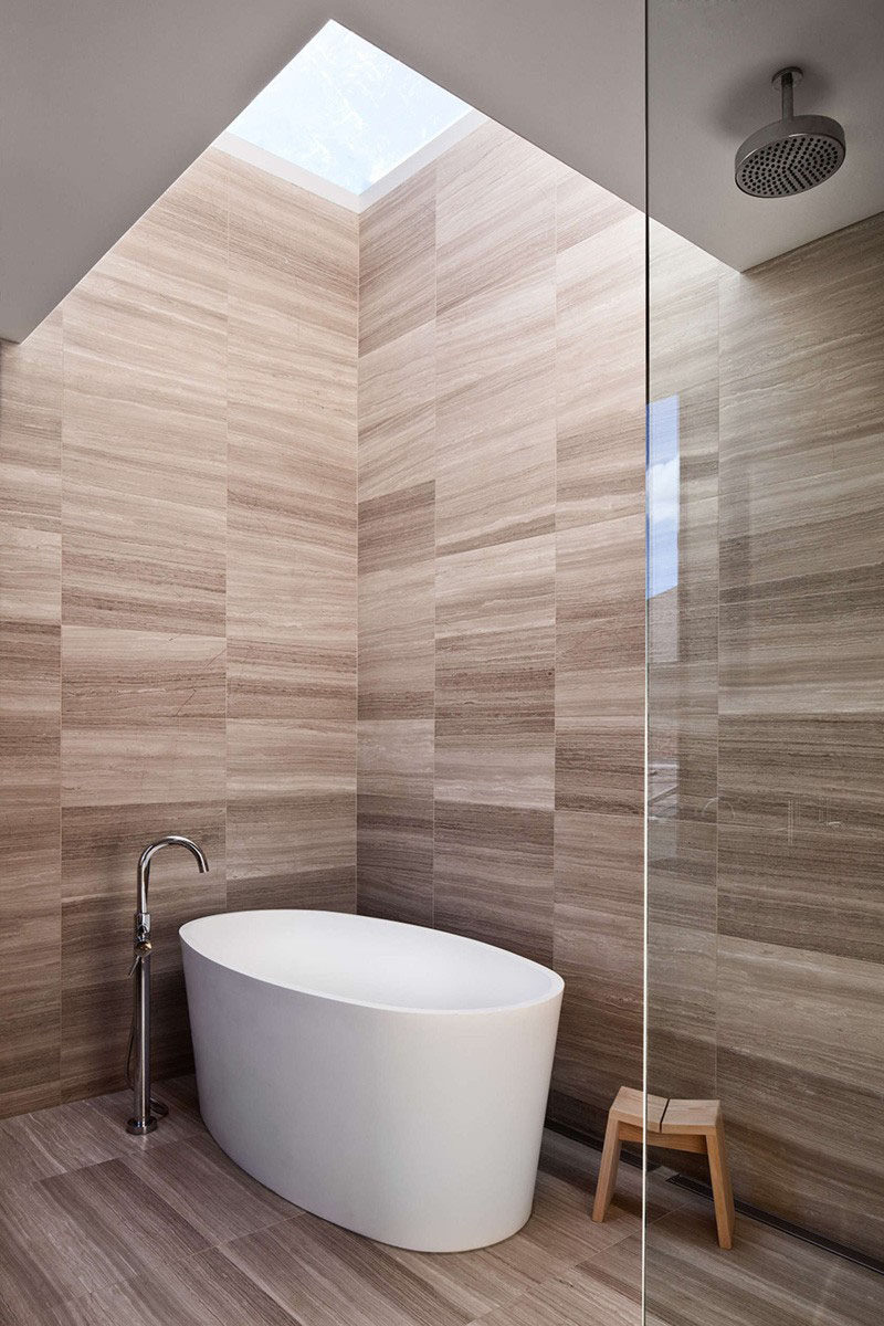 Bathroom Tile Idea - Use The Same Tile On The Floors And The Walls | The tiles on the walls and floors of this bathroom have an almost wood grain look to the them, giving the space a warm vibe.