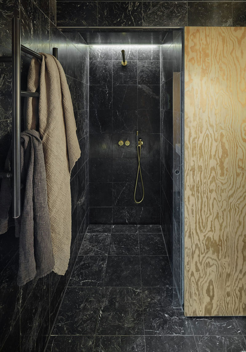 Bathroom Tile Idea - Use The Same Tile On The Floors And The Walls | Black marble tiles on the floor, walls, and ceiling of this small bathroom, coupled with the cold and black hardware give the space a luxurious look.
