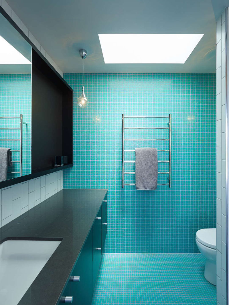 tiny bright blue tiles cover the floor and one of the walls in this bathroom to add a bold punch of color
