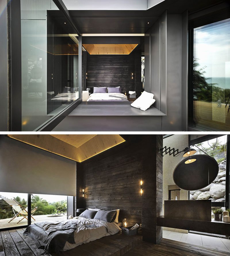 Looking into this modern bedroom through a large pivoting window, the blackened wood accent wall is a bold statement, while the lighter wood and hidden lighting in the ceiling draws your eye upwards, making the room appear larger than it is.