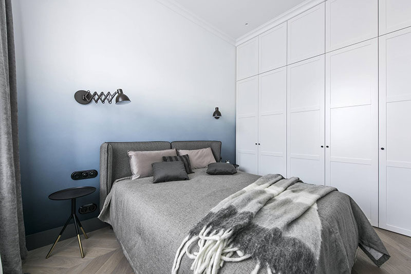 This modern bedroom design features a soft blue ombre accent wall, grey bedding and curtains, and a wall of floor-to-ceiling white cabinets.