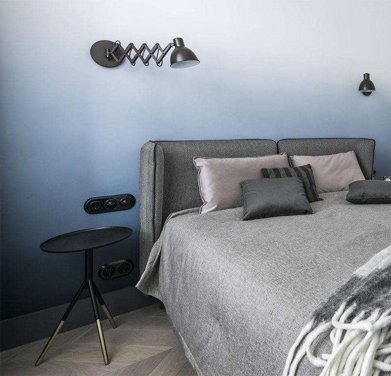 This modern bedroom has a soft blue ombre accent wall behind the grey upholstered bed.