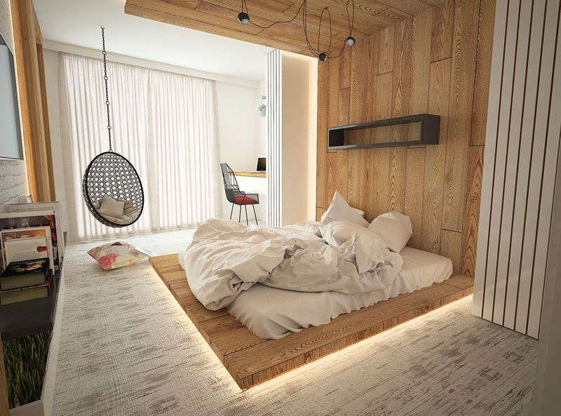 Installing hidden lighting in your modern bedroom is a great idea if you want to create a warm soft glow throughout your room. In this bedroom, hidden LED lighting was used underneath and behind the floor-to-ceiling wooden headboard.