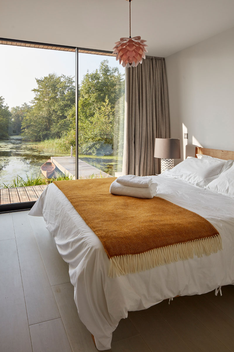 This modern bedroom looks out onto the lagoon through the floor-to-ceiling windows.