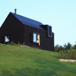 This small black house sits on a slope in the Croatian countryside