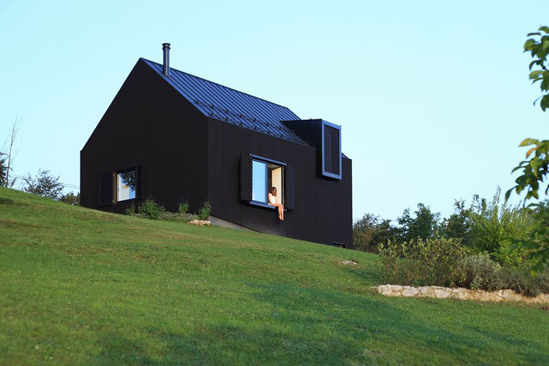 This small modern black house sits on a slope in the countryside of Croatia.