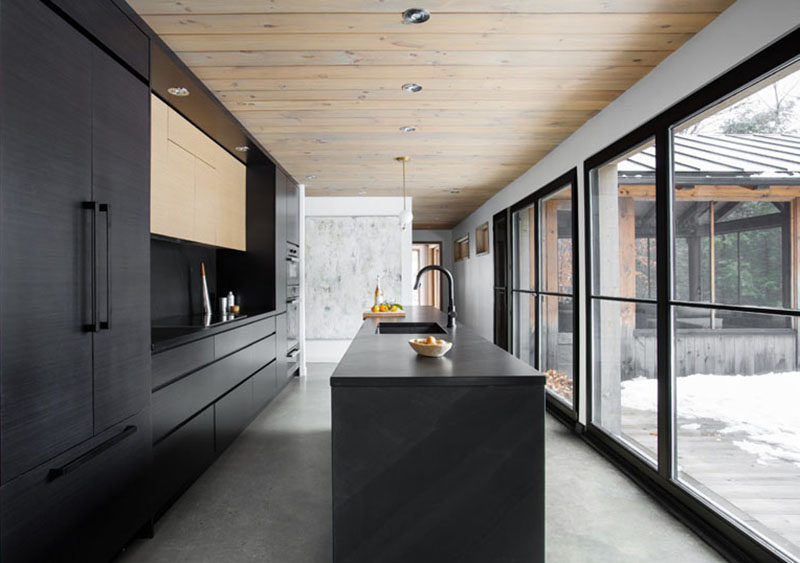 This modern black kitchen stands out against the light floors and white walls, and fits right in with all of the other black elements found in the home.