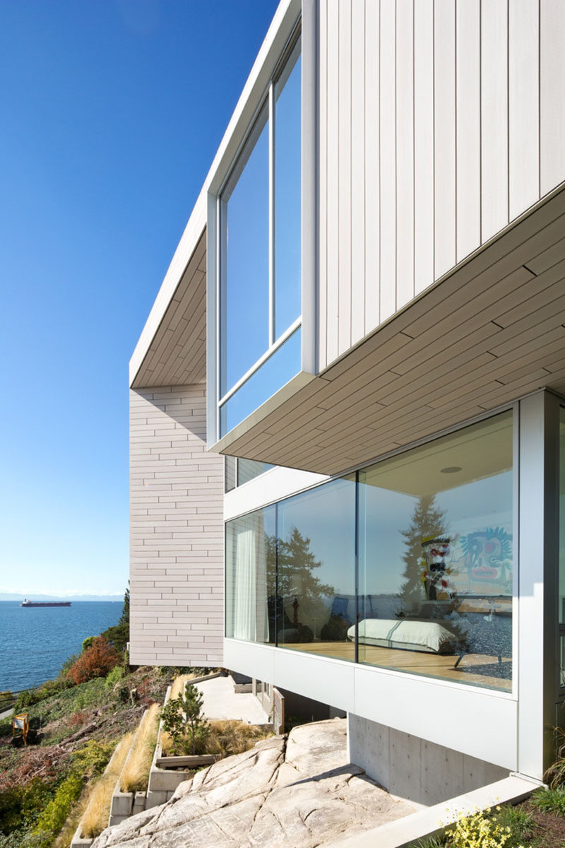 This concrete and wood modern house with light wood siding, has large windows to enjoy the ocean view.