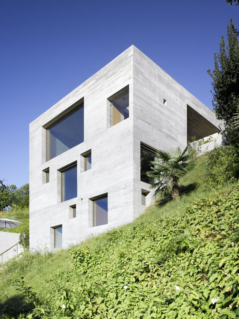 13 Modern House Exteriors Made From Concrete | Square cutouts for the windows on the exterior of this concrete house create a patterned look that's accentuated at night when light shines through the windows.