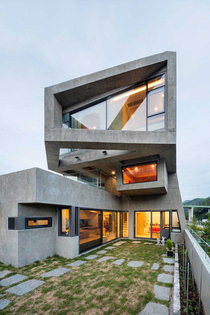 13 Modern House Exteriors Made From Concrete | Smooth concrete has been used for the exterior of this home and and is brightened by the warm light that shines through the windows.