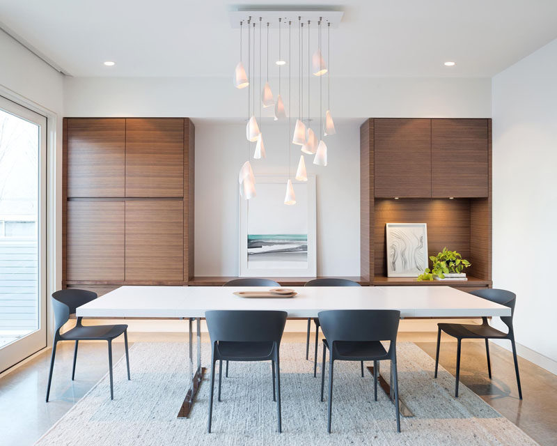 In The Dining Room Sculptural Pendant Lights Hang From Ceiling While Built Walnut Cabinets Create Plenty Of Storage E