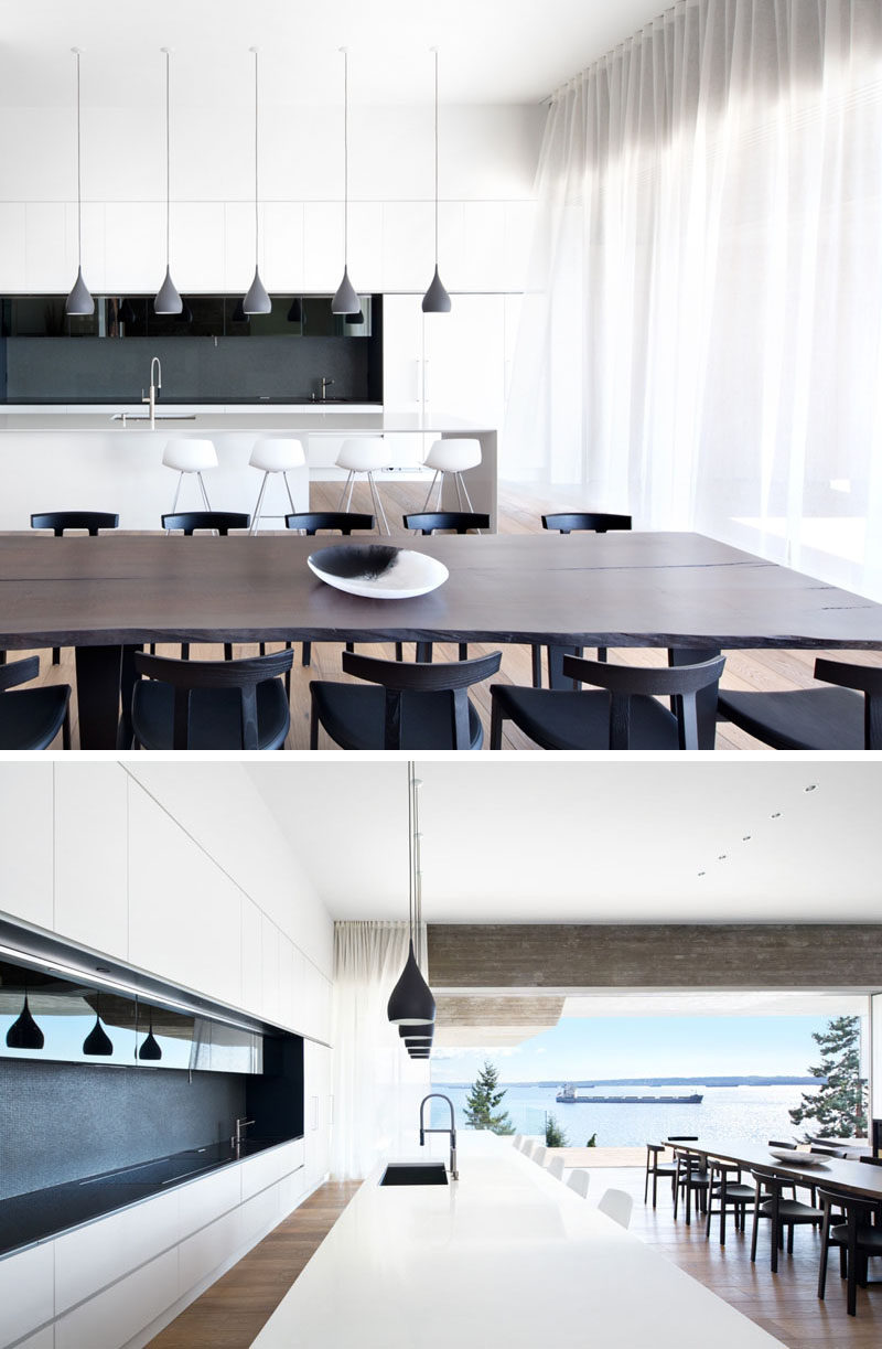 This modern dining room with a live-edge wooden table is surrounded by black dining chairs, and beside it, the kitchen has bright white cabinets, a central island lit with pendant lights and a dark grey and black backsplash.