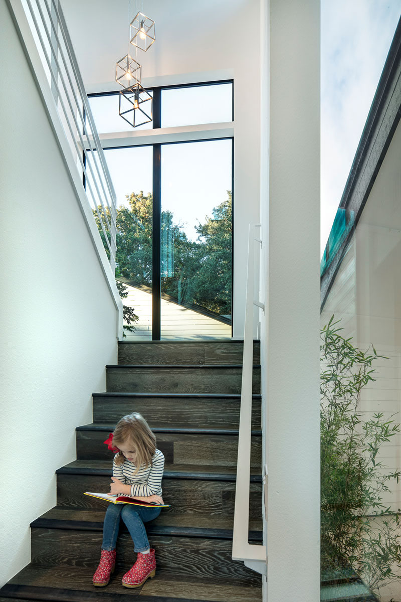 These wood and white stairs have lots of natural light from the large windows.