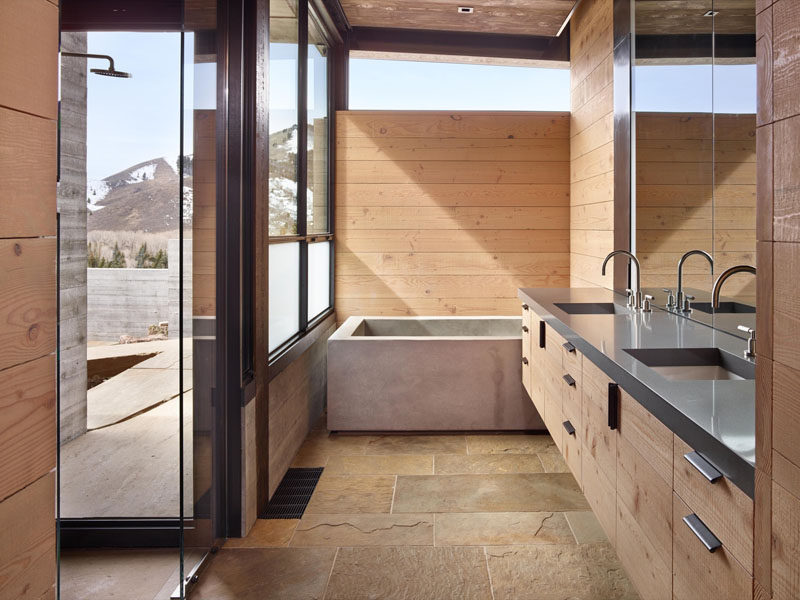 In this industrial modern bathroom, wood and stone tiles have been paired with a concrete bathtub. In the shower, there's a floor-to-ceiling window so that you can have mountain views while relaxing.