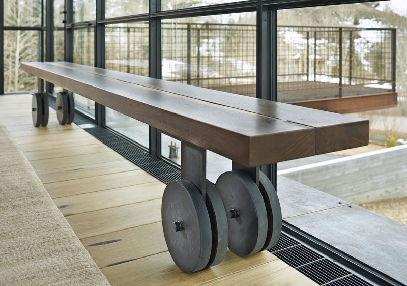 A wooden bench continues the industrial theme throughout the house with steel wheels attached to the legs.