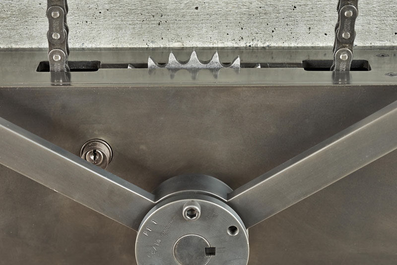 Industrial elements like this hand-crank wheel are used in the design of this house to open a large pivoting glass wall.