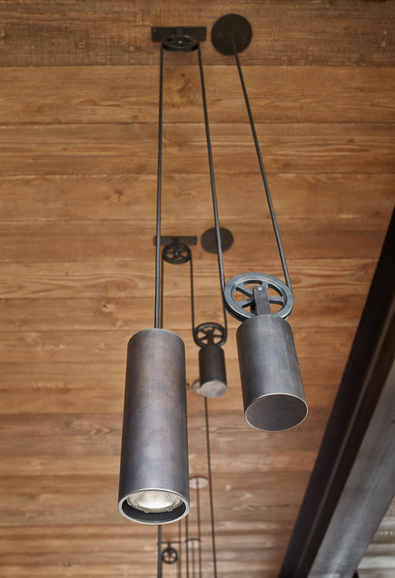 These industrial steel pendant lights are hung using a pulley system.