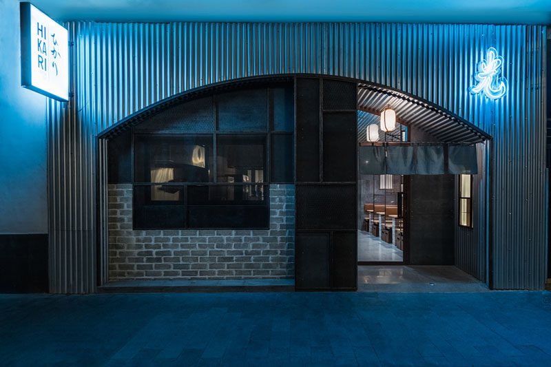 Industrial Interior Design - This Restaurant and bar goes for a warehouse chic style with metal, concrete, and wood. Designed to look like the entrance to a Tokyo tunnel, the facade of this modern restaurant features steel, brick, and neon signage to create an industrial yet inviting exterior.