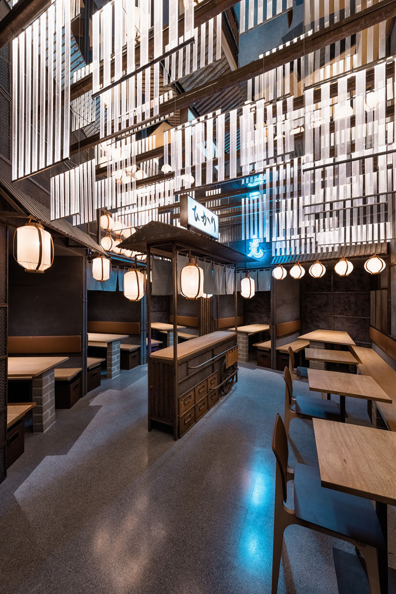 Industrial Interior Design - This Restaurant and bar goes for a warehouse chic style with metal, concrete, and wood. Inside the square dining room of this modern restaurant, lighted boards hang from the ceiling as a nod to the neon signs that light up the Tokyo night sky. Lanterns hang from the eaves created by steel panels over each of the dining spaces, casting a warm glow in the industrial space.