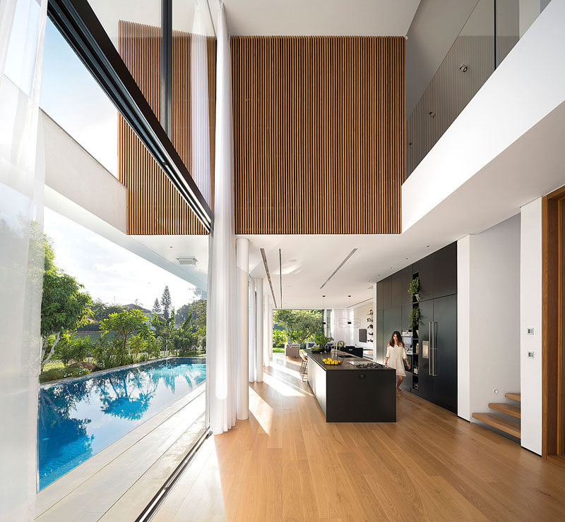 This modern house has a foyer with a double-height ceiling that provides views of a section of the upper floor that's covered in cedar.