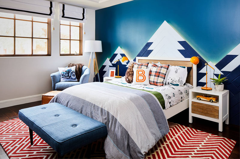 This kids bedroom design includes a mountain range as wall art, with hidden lighting that mimics the colors of the Northern Lights.