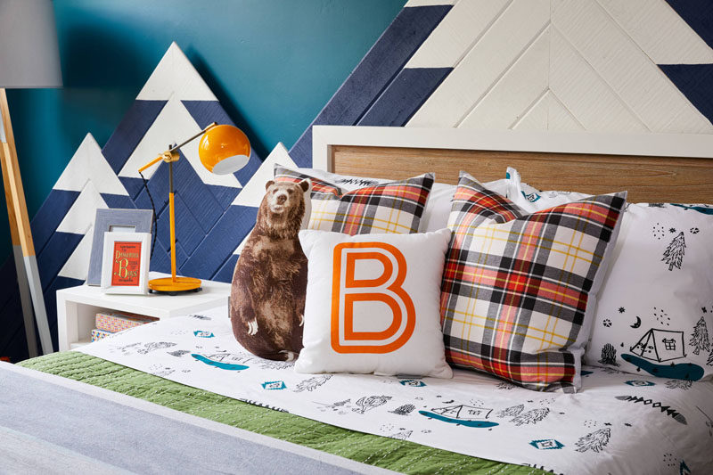 This kids bedroom design includes includes elements from the great outdoors, like a mountain range with hidden lighting that mimics the colors of the Northern Lights, camping inspired sheets, and a grizzly bear throw pillow.