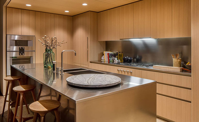 This modern kitchen features honey-hued American oak cabinets with satin-finish stainless steel countertops and backsplashes. Dornbracht faucets have been used for the sink, and for the floor, light colored quartz has been used in the kitchen, while oil finished oak flooring has been used in the rest of the apartment.