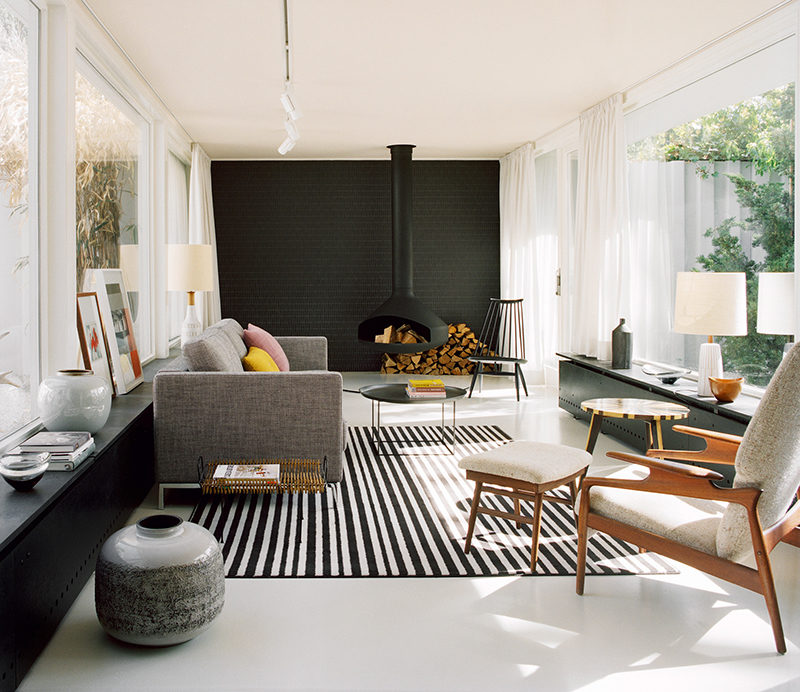 A Hanging Fireplace And Black Accent Wall Stand Out In This Modern Living Room