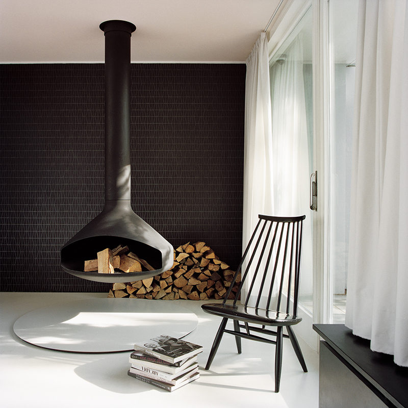 In this modern living room, a hanging fireplace matches the black tile accent wall and the several pieces of black furniture.