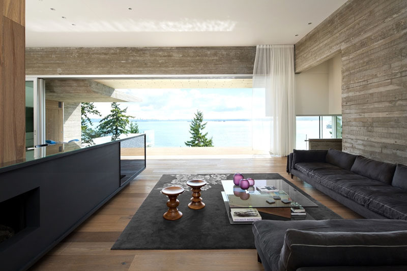 In this modern living room, a low profile sofa and dark rug define the area, while the television is is tucked into a cabinet. The living room also opens up to the deck outside.