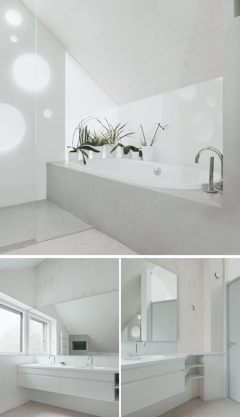 The white and light concrete bathroom in this modern home is simple in its design. There's a built-in bathtub, a glass enclosed shower and an angled vanity.
