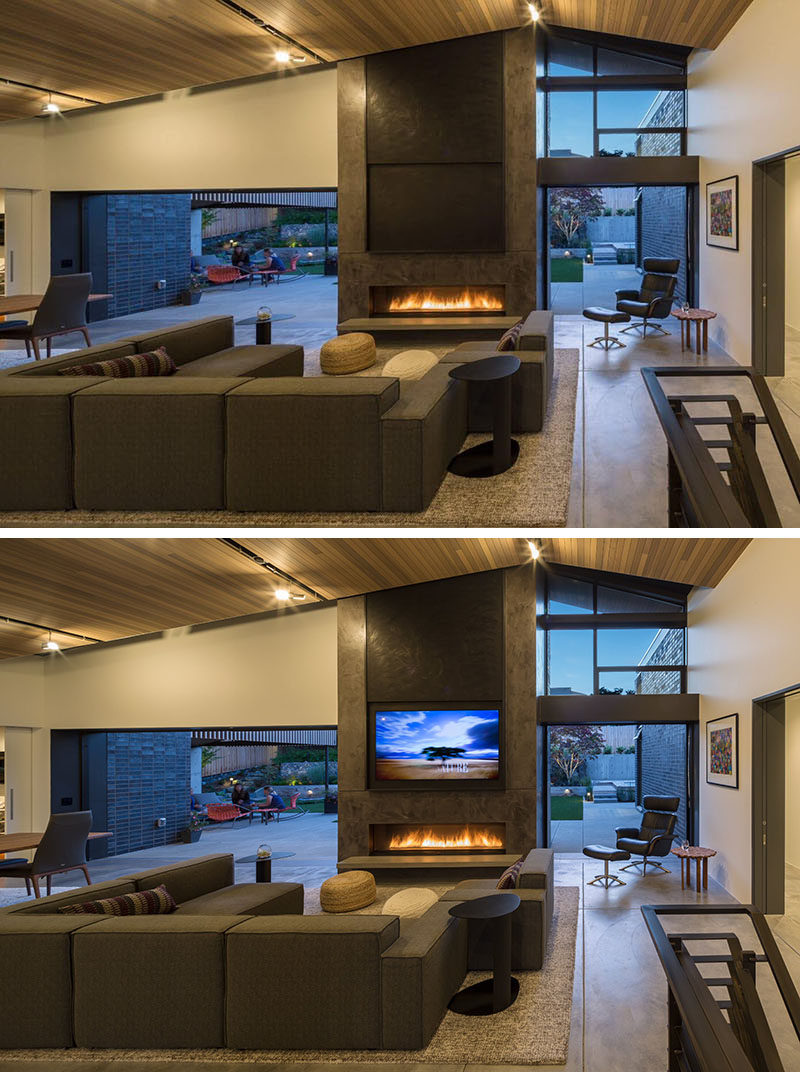 Inside this modern home, there are sliding glass pocket doors that disappear into wall to create an indoor/outdoor living experience. The living room has a vaulted tongue and groove cedar ceiling. Sitting above the gas fireplace is a motorized panel that can be raised to reveal the television.