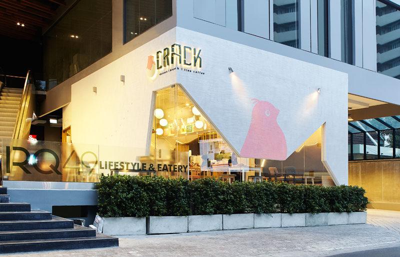 This modern dessert restaurant in Bangkok, Thailand, has an angular facade, much like a cracked egg shell.
