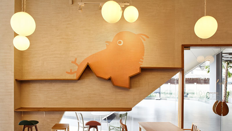 This chick breaking free from its shell on the wall of this modern restaurant, also incorporates a wooden shelf.