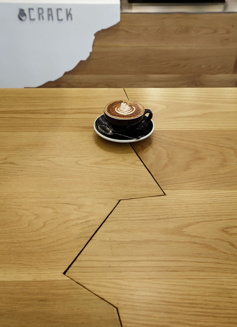 The wooden table in this restaurant with a 'crack' in it fits with the theme of the restaurant.