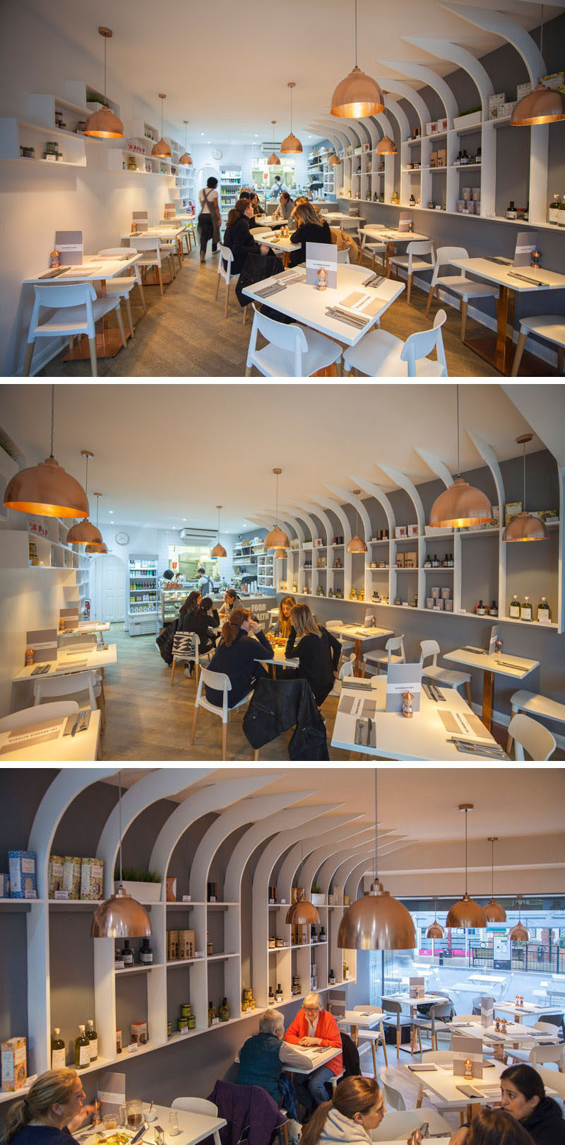 In this modern resturant interior, the designers used white for the walls, furniture, and shelves, wood on the floors and chair legs, copper accents in the form of light fixtures, table stands, and salt and pepper shakers. A grey accent wall is used to draw your eye to the white shelves.