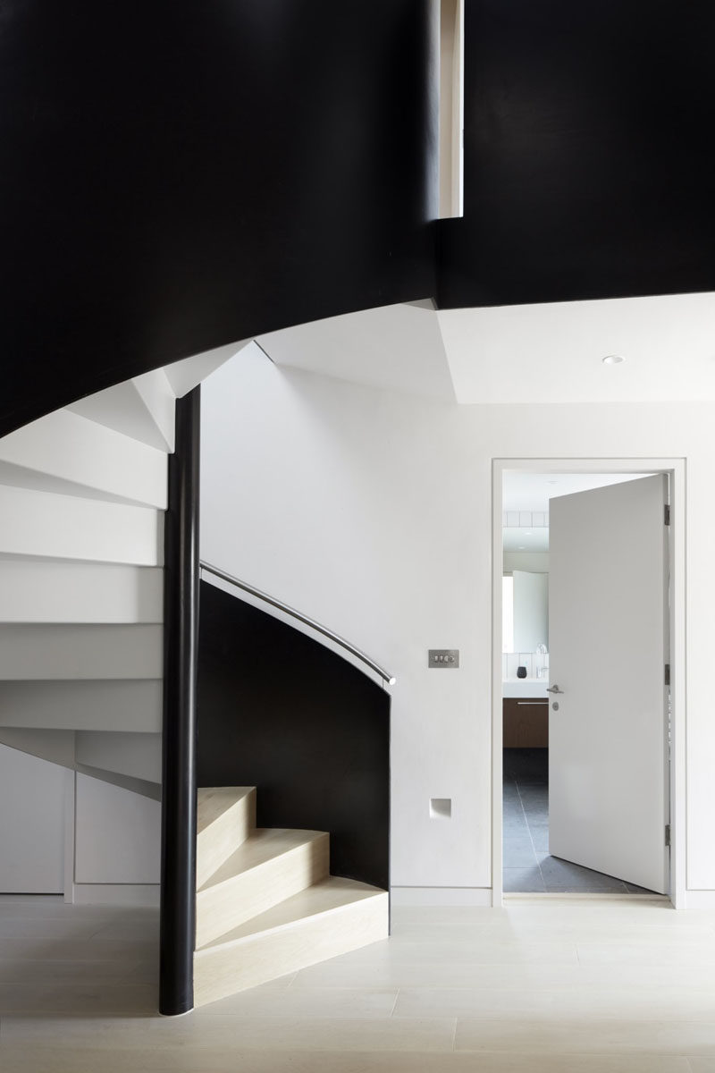These spiral stairs have a color palette of black, white and wood.