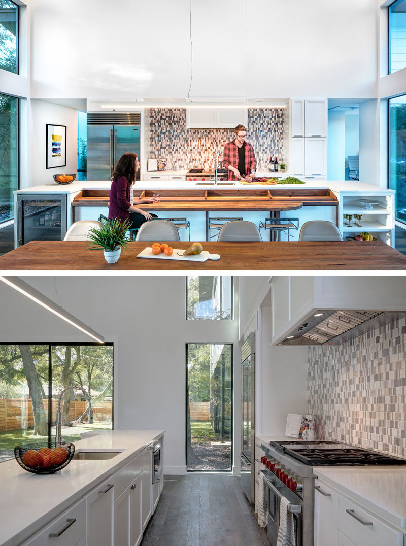 This modern kitchen has a large island with a built-in wood bar, and at one end there's a small drinks fridge, and at the other end is open shelving. White cabinets keep the space bright and patterned tiles used for the backsplash add an artistic touch.